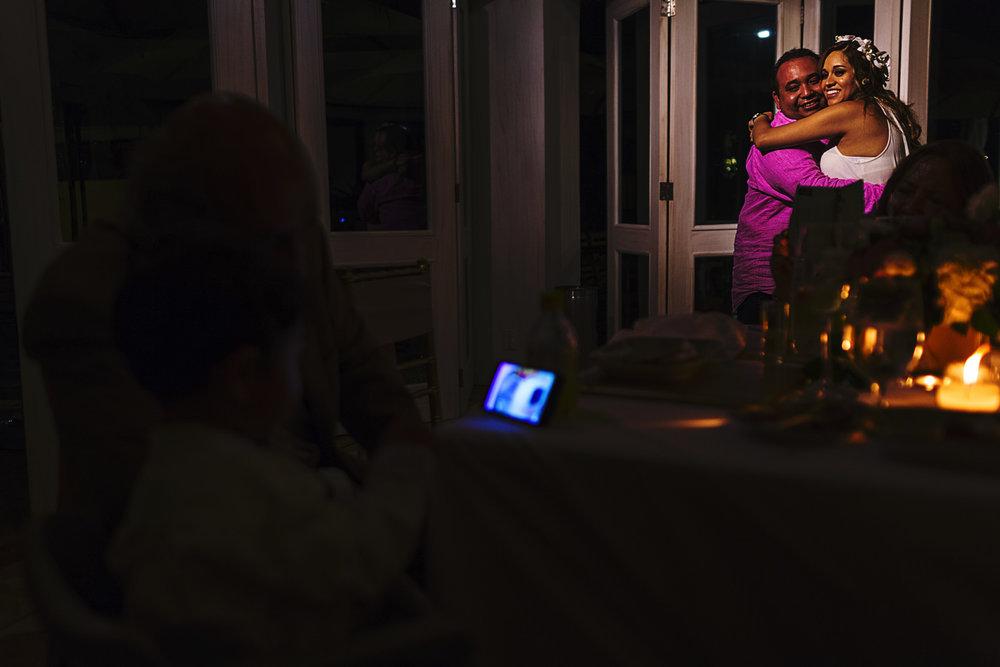 Pareja en su primer baile en la recepción de la boda mientras su hijo mira videos en un teléfono celular