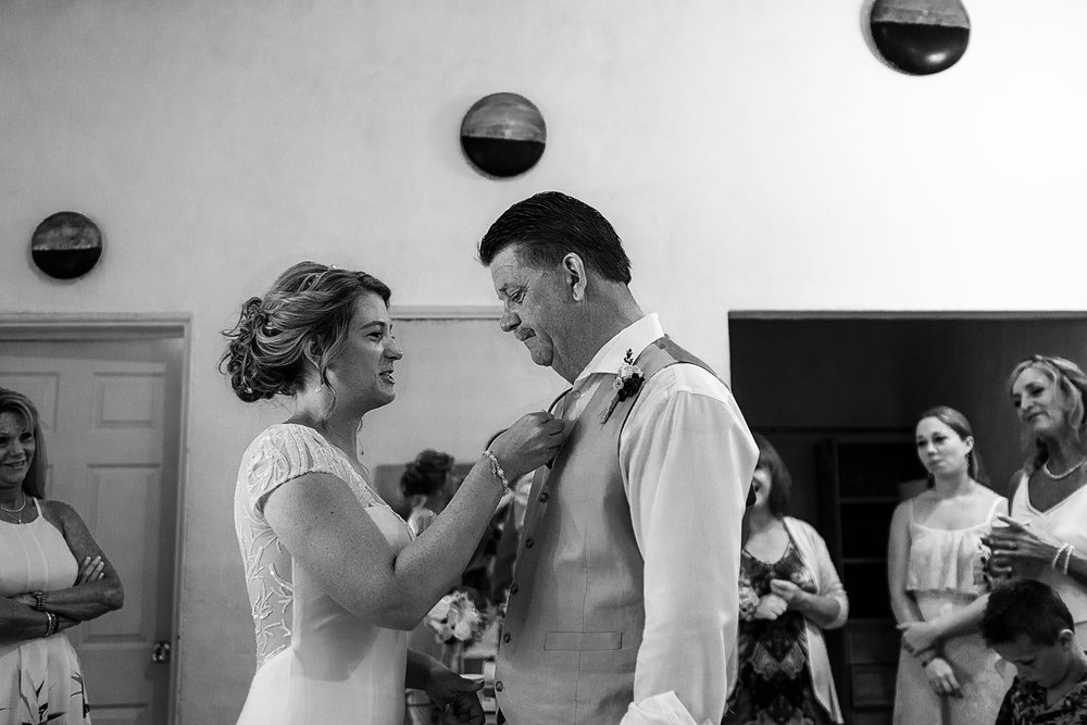 Bride fixing her father's suit and tie