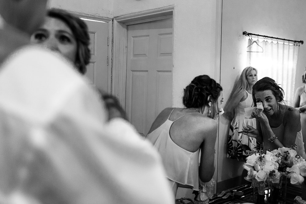 Sister of the bride whipping the tears out her eyes against the mirror
