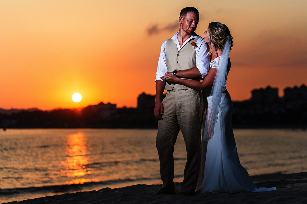 Wedding couple's portrait standing on the beach at Martoca Beach Garden with sunset behind them