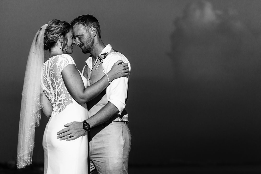 Black and white portrait of groom and bride standing face to face against the sky