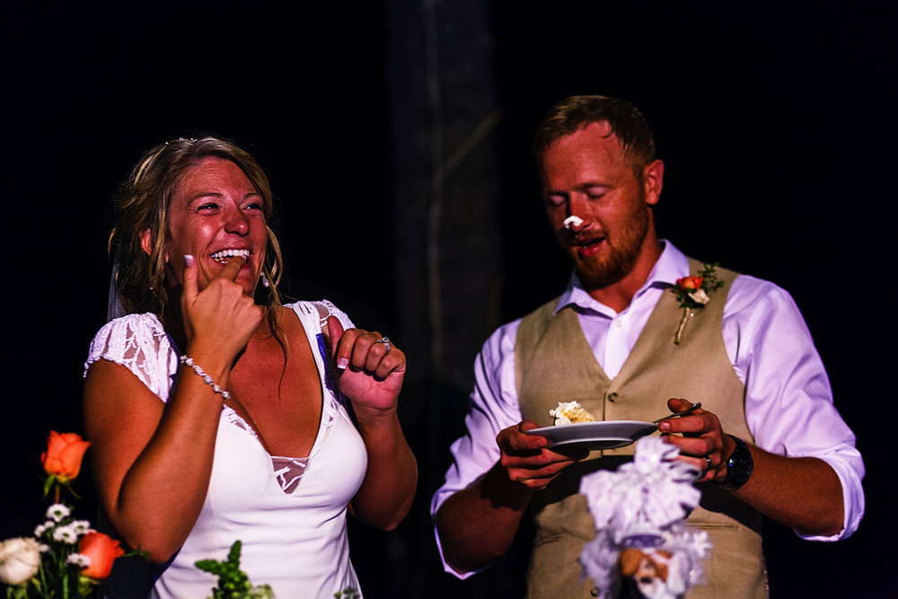 Bride laughing after putting some wedding cake on the groom's nose