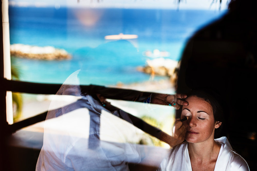 Bride having her make-up in front of a window with the reflection of the ocean