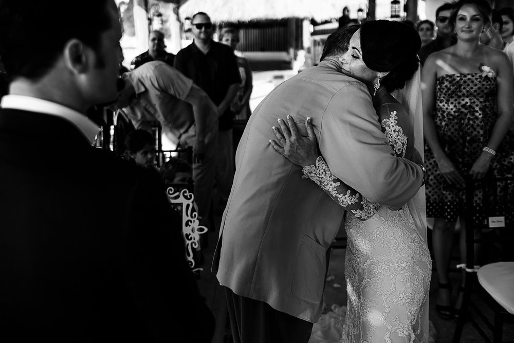 Father of the bride hugging the bride at the altar