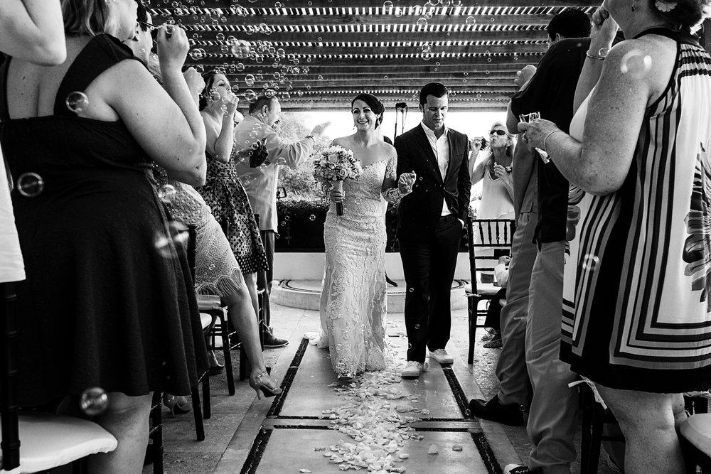 Groom and bride walking out the ceremony whilst guests blow bubbles