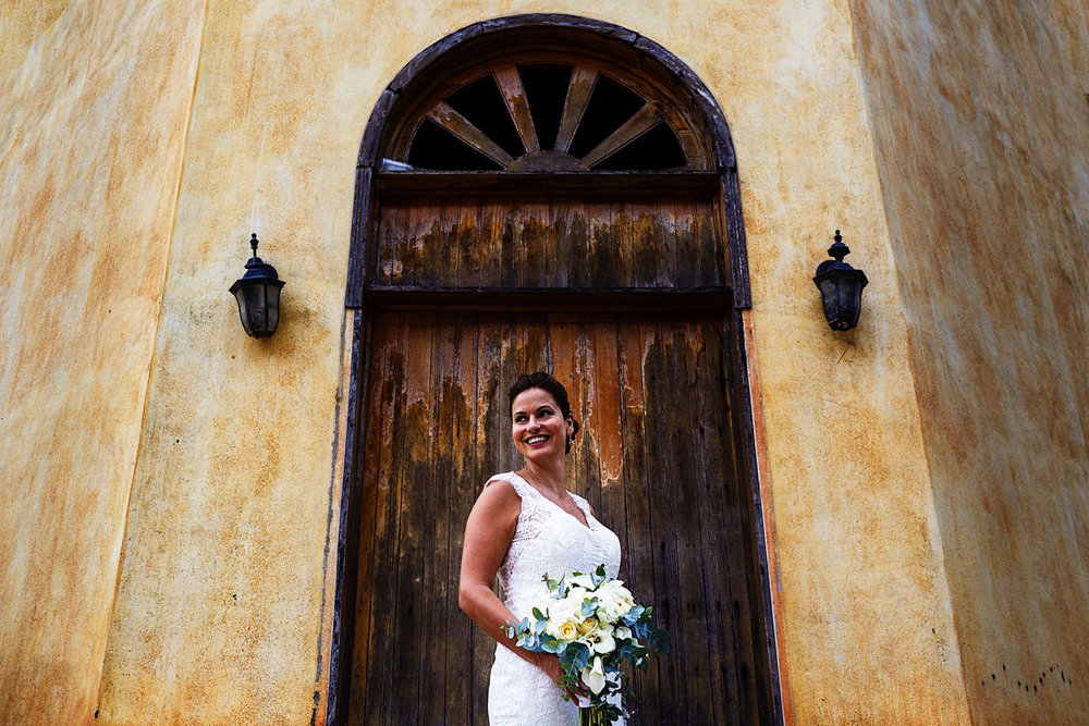 Portrait of the bride on a door outside a tequila factory