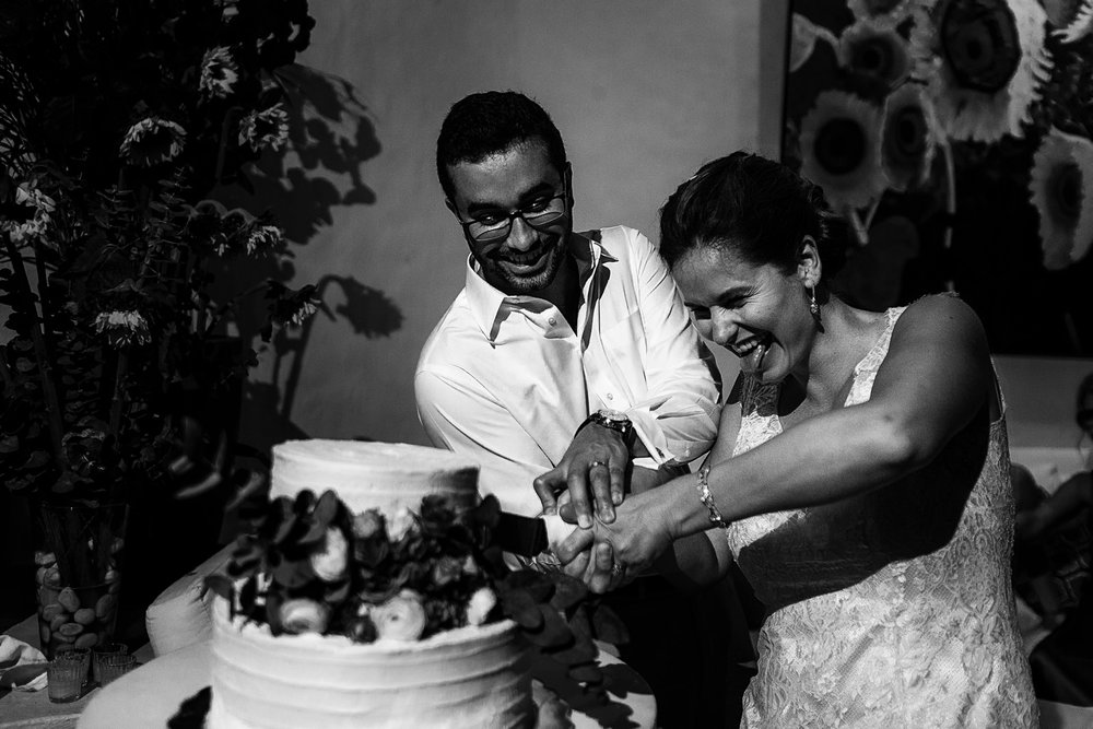 Bride sticking out her tongue as the couple is cutting the cake