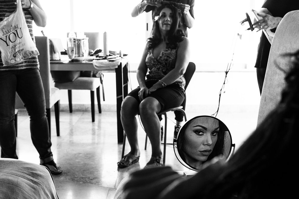The bride's face is on the mirror and at the background her mother is getting her hair done
