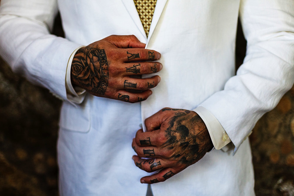 The tattooed hands of the groom are holding his suit's coat