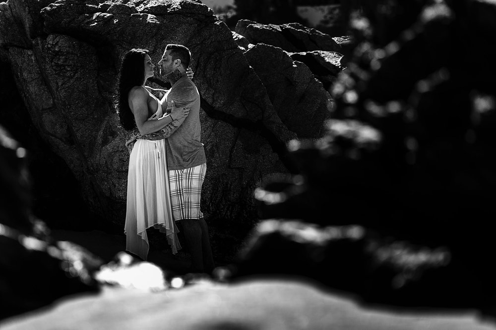 Couple about to kiss hidden in the rocks of Conchas Chinas beach