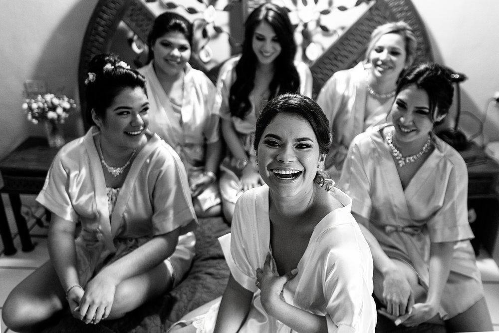 Novia y damas sentadas en la cama en batas antes de comenzar a vestirse para la ceremonia religiosa de la boda