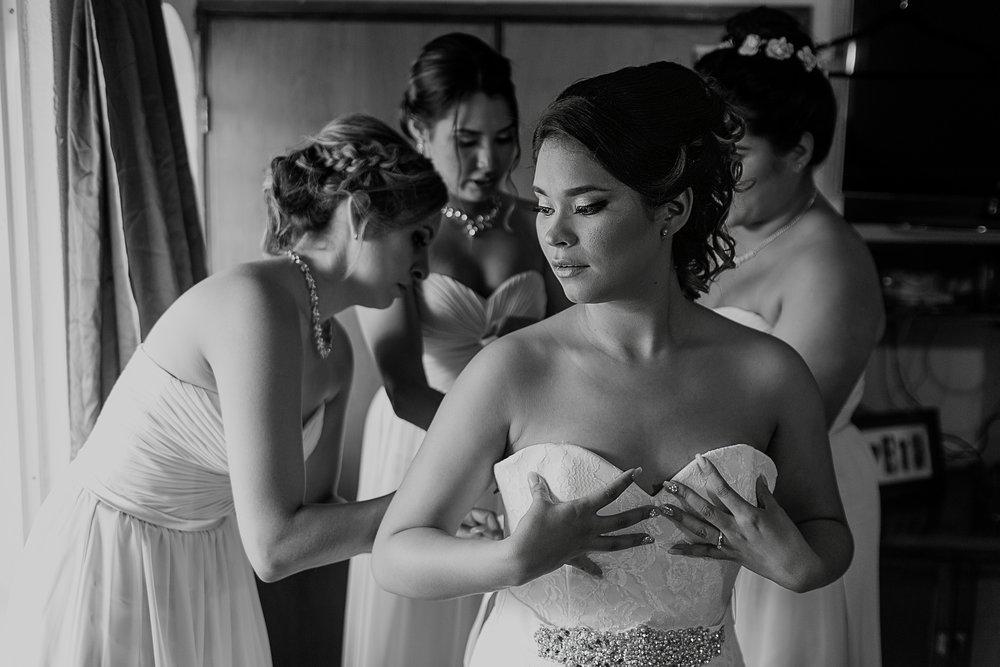 Damas ayudando a la novia a ponerse su vestido