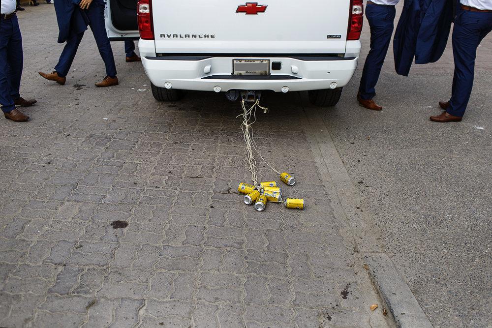 Los amigos del novio llegando a la iglesia en una camioneta que lleva como sonaja unas latas de cerveza pacifico atadas a la cola del vehículo
