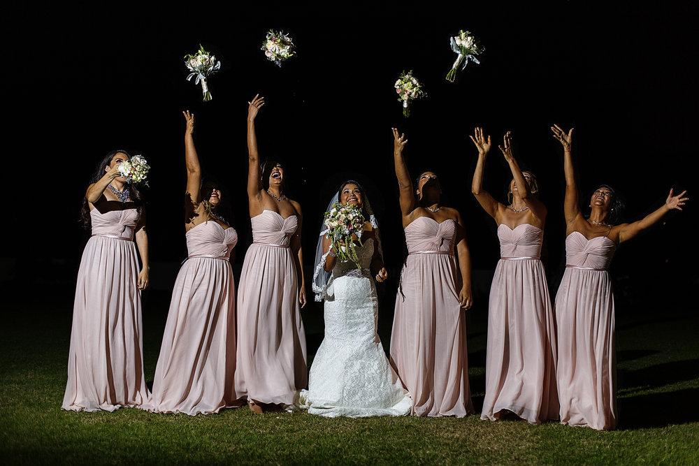 Retrato de la novia con sus damas lanzando los ramos al cielo