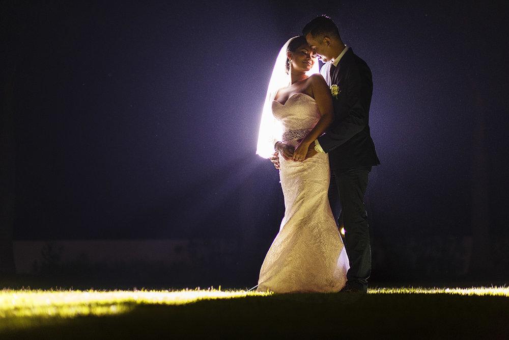 Pareja parada en el pasto de noche, el novio abraza por detrás a su novia