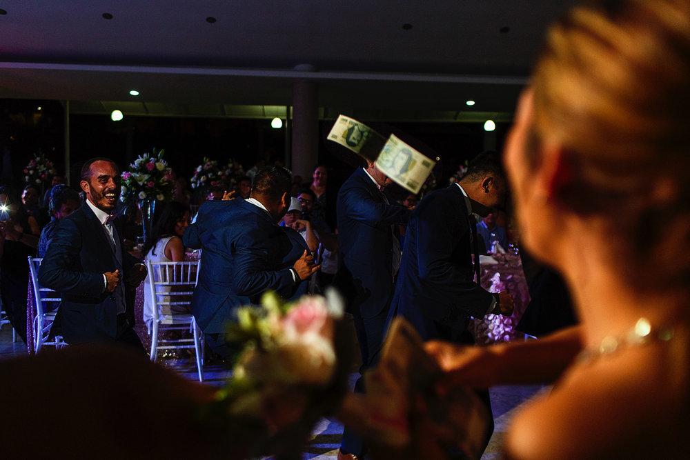 Las damas avientan billetes a los amigos del novio durante un pequeño baile como entretenimiento y presentación de la pareja en la fiesta de la boda