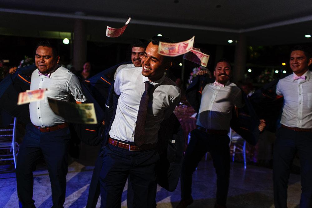 Novio y amigos bailan y se quitan el saco del traje mientras hay billetes volando arrojados por las damas durante la fiesta de la boda