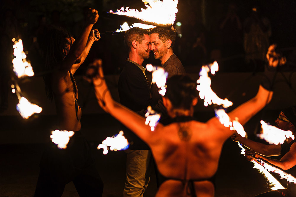 Gay couple in the middle of fire dancers as part of the entertainment during the rehearsal dinner celebration