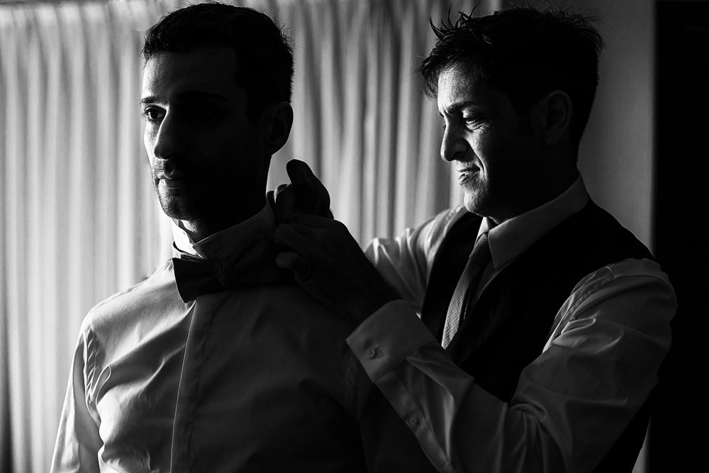 Groom helping his partner with the bow tie before the ceremony on their wedding day