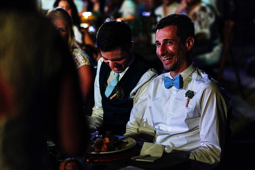 Grooms laugh as reaction while wedding guest is giving a toast speech during the dinner at Casa Karma