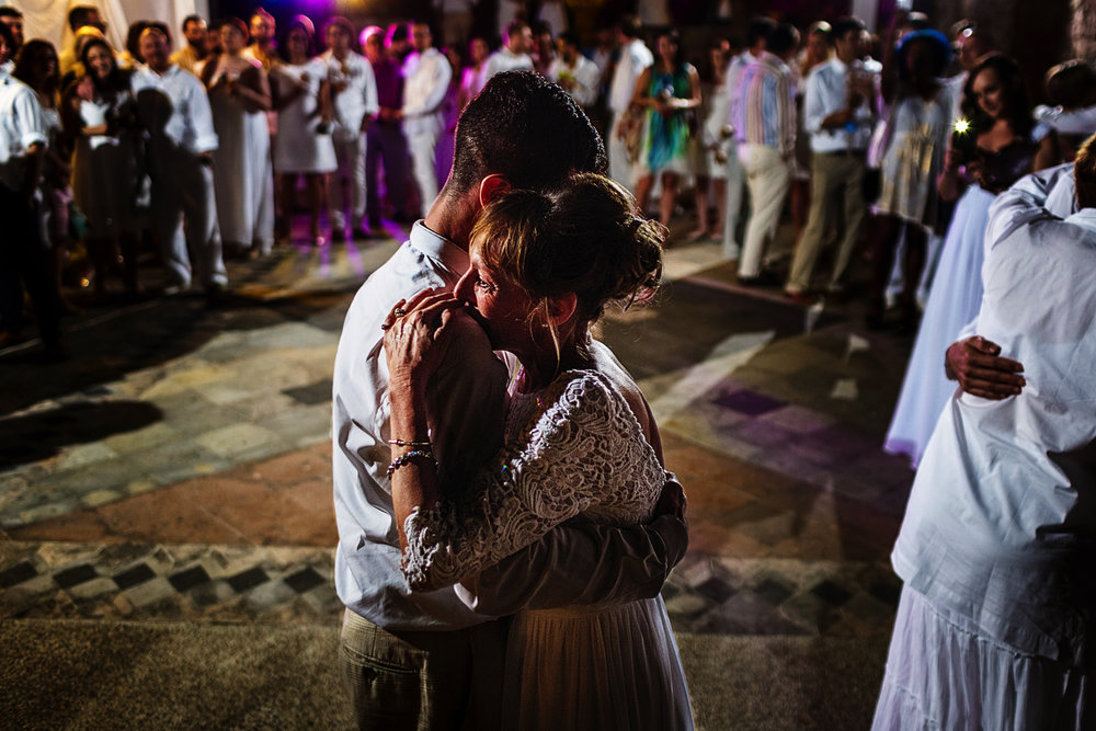 Groom and mother dance in wedding reception in the middle of all the guests and family