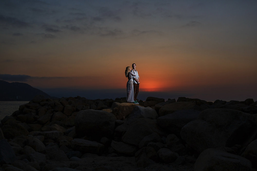 Wedding couple standing on the top of the rocks near the ocean in the Mexican pacific during the sunset