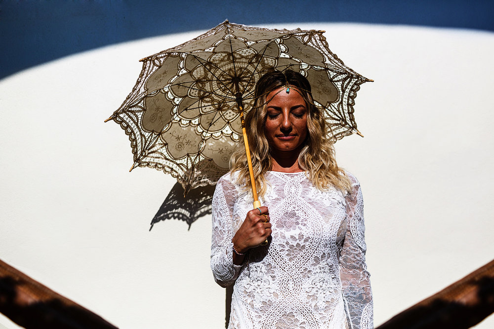 Bride portrait holding a knitted umbrella under a blue arch shadow