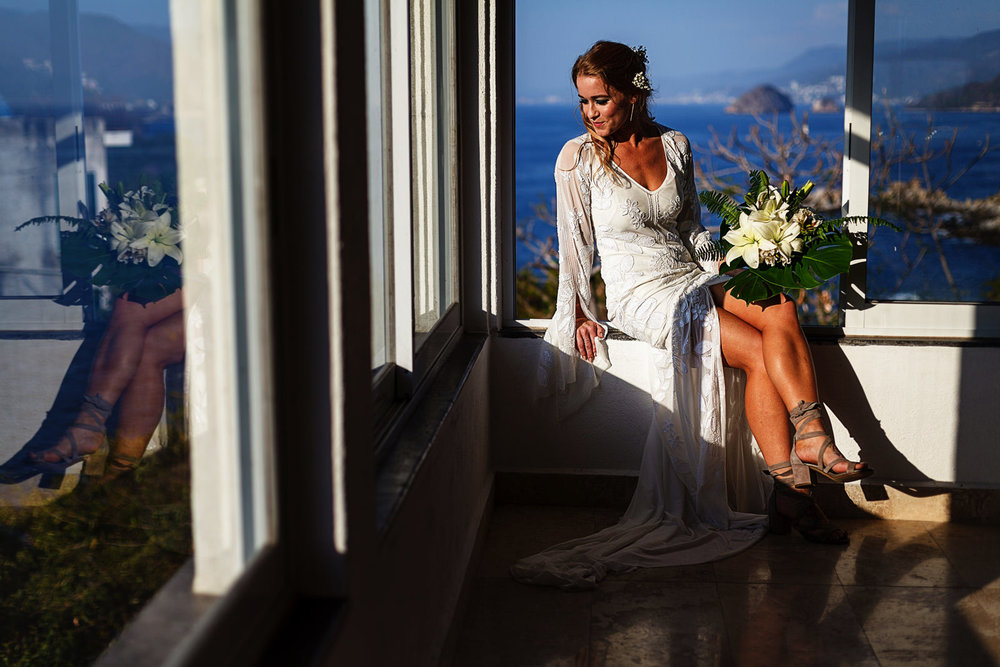 Portrait of a bride sitting on the edge of a window, Los Arcos can be seen in the background