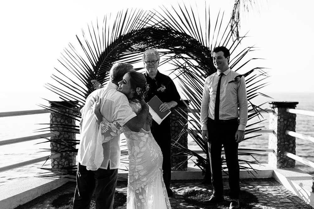 Bride and father hug as he gives her away at the end of the aisle before the wedding ceremony