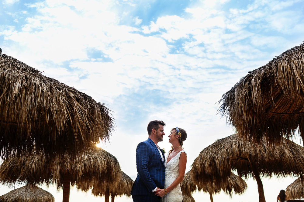 Bride and groom standing between beach palapas at Hyatt Ziva resort in Puerto Vallarta, Mexico