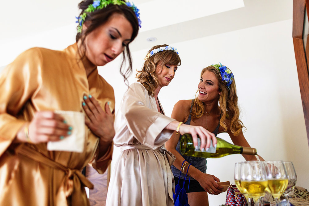 Bride serving champagne into a glass during the make-up and hair preparations in the bridal suite before the destination wedding ceremony