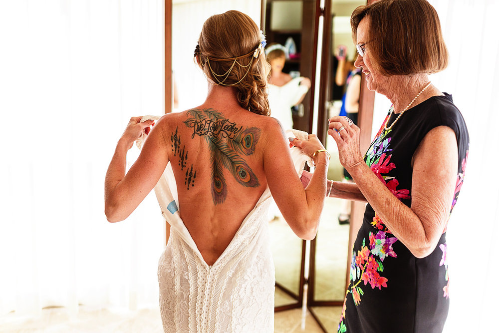 Bride putting her wedding dress on right next to her mother