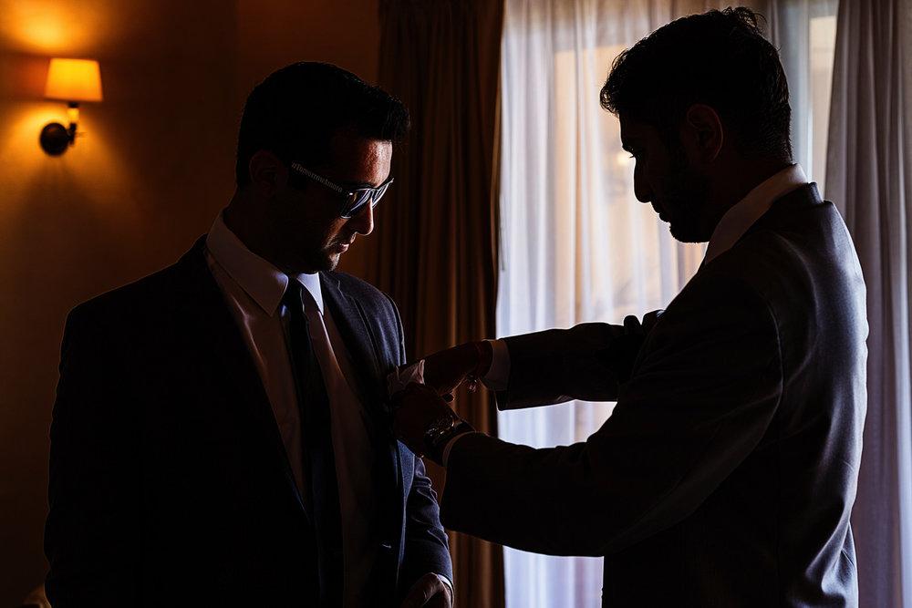 Groomsmen helping with handkerchief to the groom.