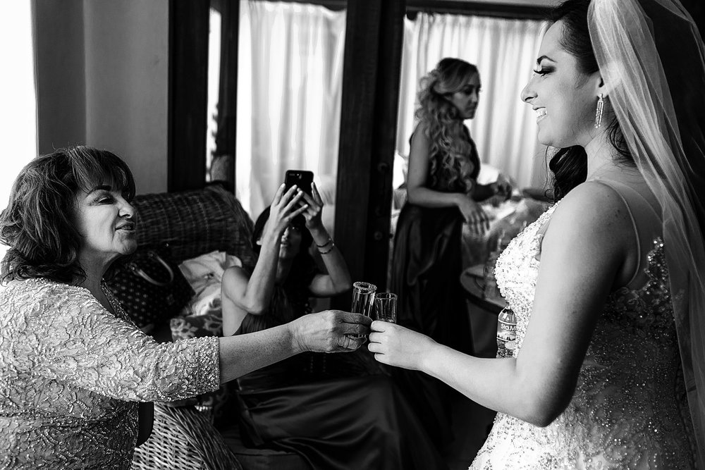 Bride and her mom toasting with tequila shots before the wedding ceremony at the bridal suite.