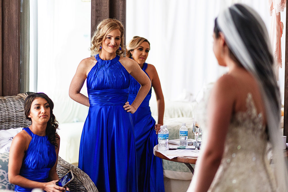 Bridesmaids stare at the fully dressed and ready-to-go bride.