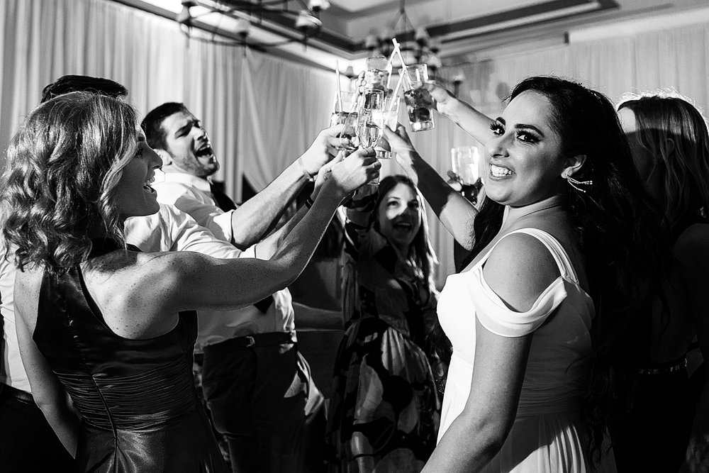 The bride toasts with friends on the dance floor.
