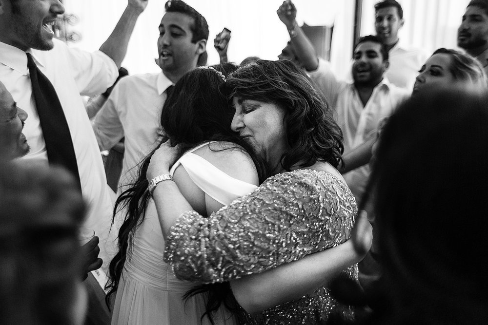 Mom hugs the bride in the middle of all the dancing of friends and other wedding guests.