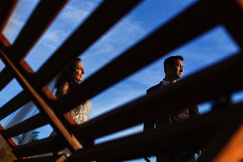 Wedding couple portrait thru a beach chair back rest, against the blue sky at St. Regis Punta Mita Resort