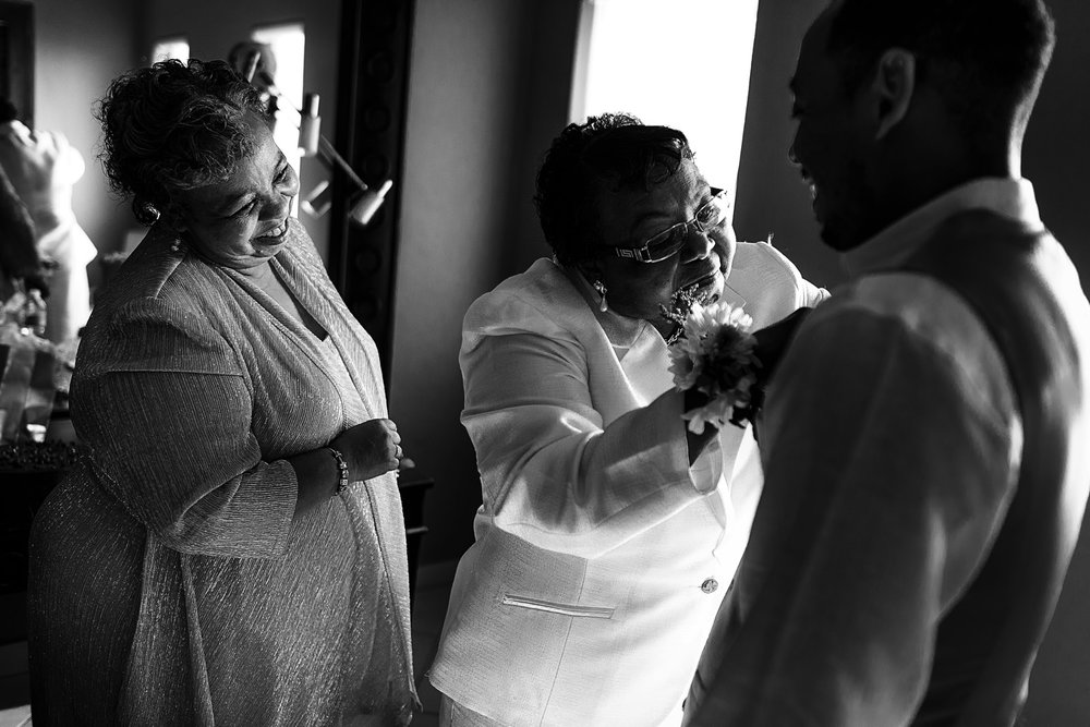 Mothers of the groom helping one of the guys to get his boutonniere on the vest.