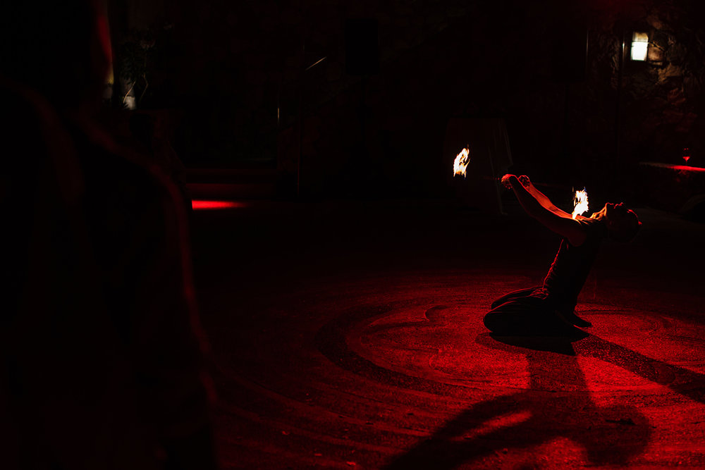 Firedancer plays with fire while kneeling down, during the destination wedding reception.
