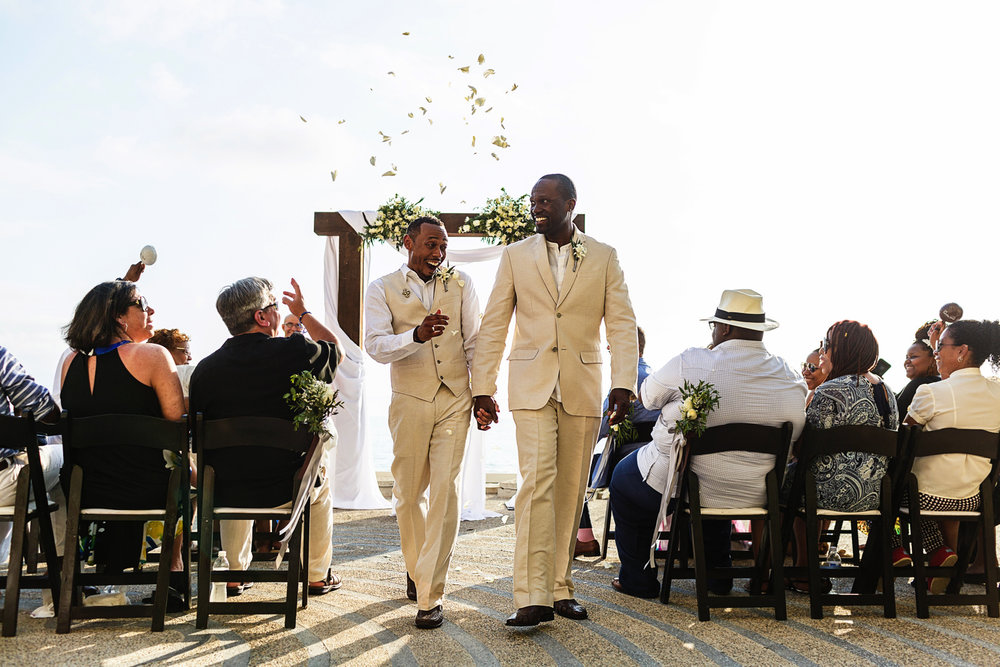 Exit from the ceremony with rose petals flying over the grooms, at the end of a LGBTQ wedding.