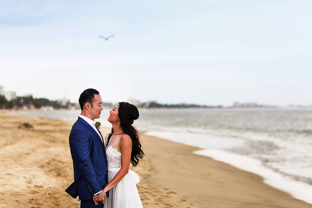 Groom and bride standing on the beach at Bucerias near the ocean with a pelican flying above them.