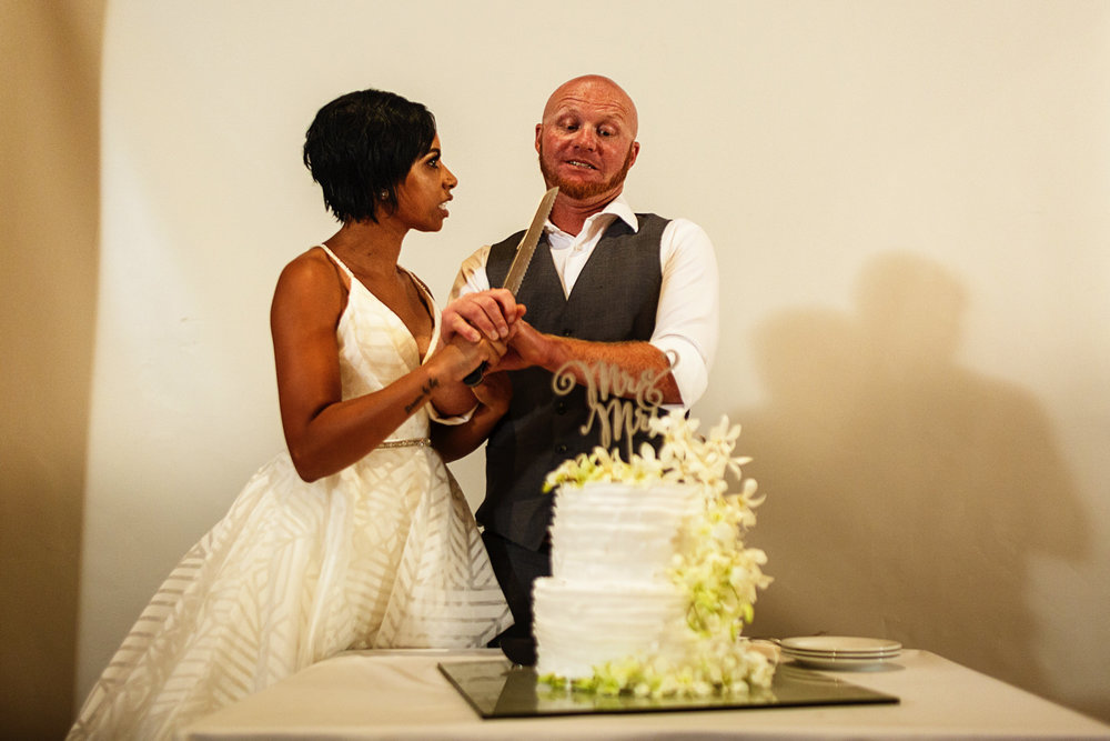 Bride threatens groom with the knife before cutting the cake