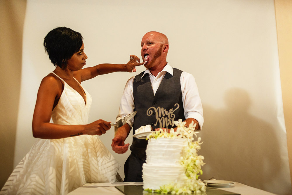Bride feeds the groom with the cake's cream