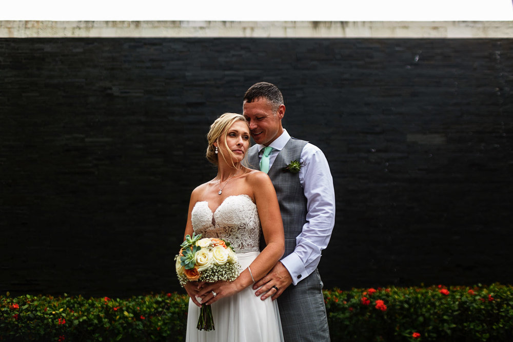 Couple standing close to each other with a dark wall waterfall in the background.