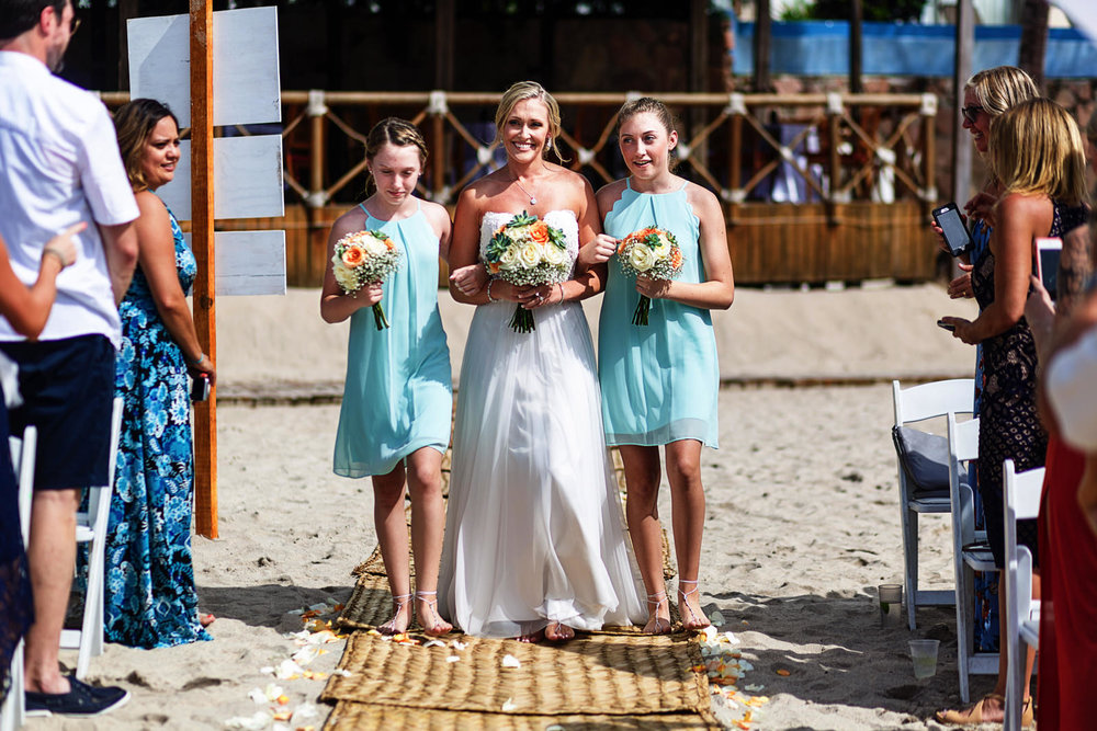 Bride and daughters bridesmaids walking down the aisle for the ceremony on the beach