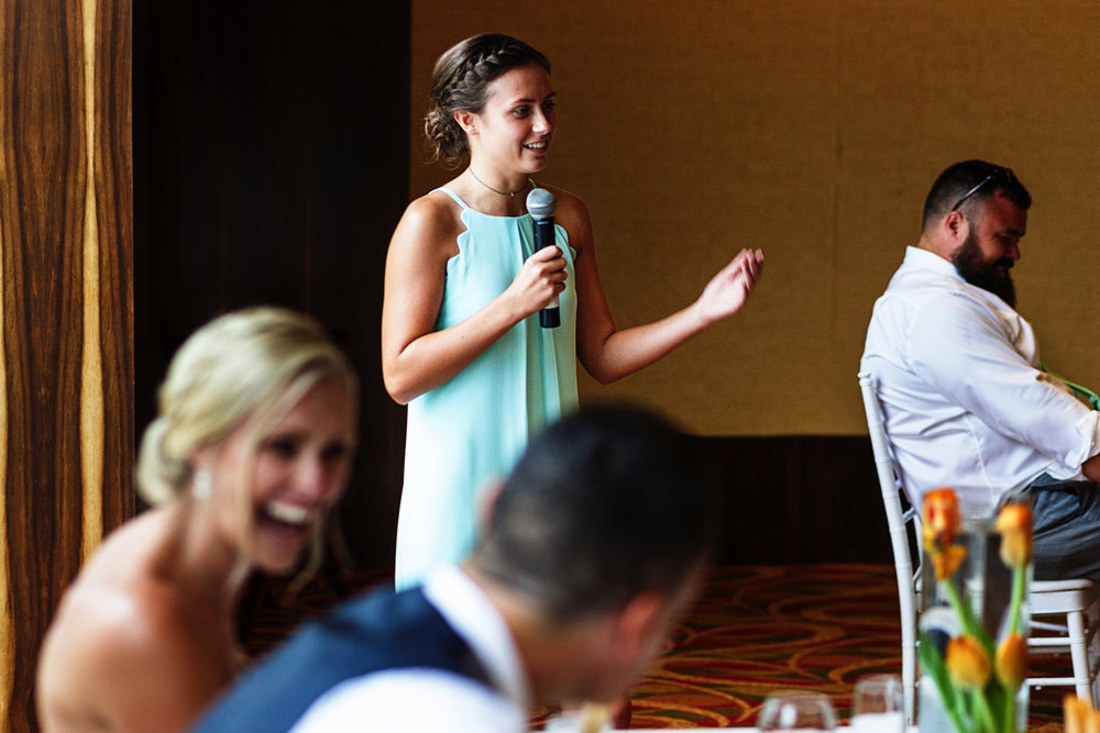 Daughter of the groom and bride and maid of honor gives a speech during dinner