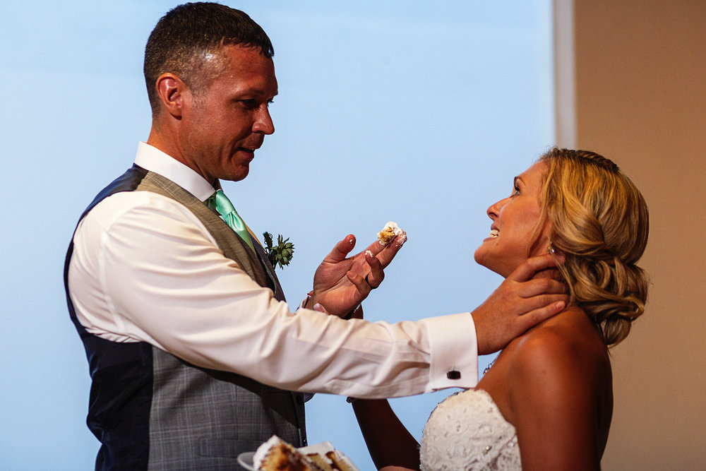 Groom grabs the bride by the neck and try to feed her with wedding cake