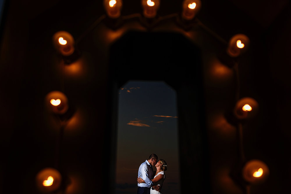 "Couple standing kissing inside a big letter ""O"" with light bulbs"