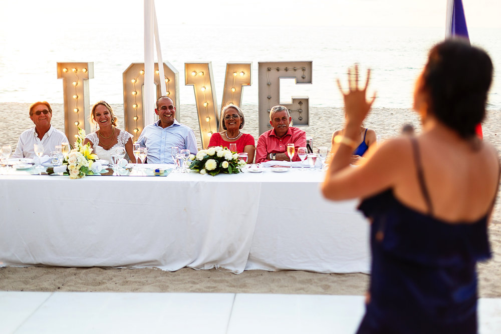 Wedding guest gives a speech to the groom and bride who sit in front of her and with a big LOVE sign behind them